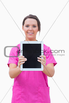 Portrait of young nurse holding out digital tablet