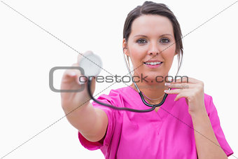 Portrait of nurse holding out stethoscope