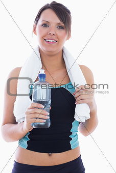 Portrait of woman in sportswear holding towel around neck and water bottle