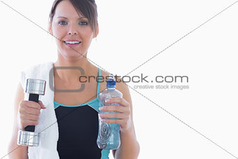 Portrait of woman holding dumbbell and water bottle