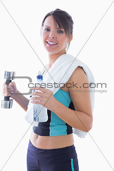 Portrait of young woman holding dumbbell and water bottle