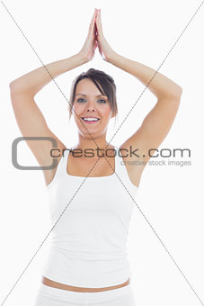 Portrait of woman in sportswear joining hands over head