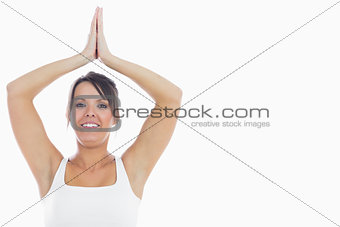Portrait of smiling woman joining hands over head