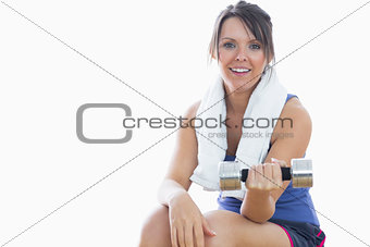 Portrait of woman sitting and exercising with dumbbell