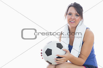 Portrait of happy woman in sportswear holding football