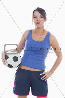 Portrait of young woman in sportswear with football