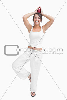 Portrait of woman doing the tree pose and holding apple