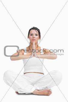 Portrait of young woman with crossed legs in praying position