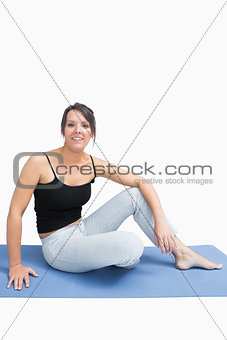 Portrait of woman in sportswear sitting on yoga mat