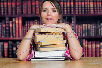 Portrait of college student sitting with stack of books in library