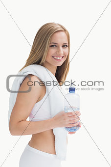 Portrait of smiling young woman with towel around neck holding water bottle