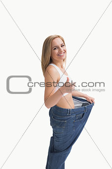 Woman wearing old pants after losing weight and gesturing thumbs up
