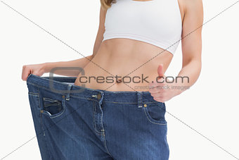 Midsection of woman wearing old pants after losing weight and gesturing thumbs up