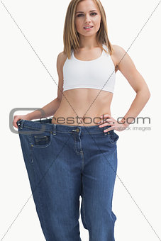 Portrait of young woman wearing old pants after losing weight