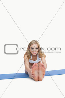 Portrait of happy woman performing stretching exercise on yoga mat
