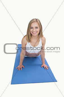 Portrait of happy woman doing pushups on exercise mat
