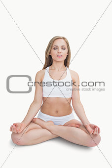 Woman sitting in lotus position with eyes closed
