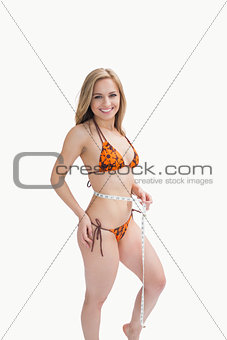 Portrait of happy young in bikini measuring waist