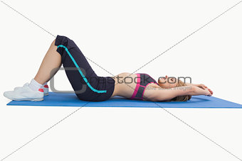 Side view of woman in sportswear lying on yoga mat