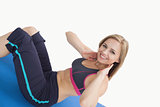 Portrait of happy young woman doing situps on exercise mat