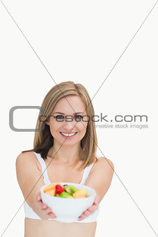 Portrait of woman offering you bowl of fruits