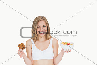 Portrait of happy woman holding cookie and fruit bowl