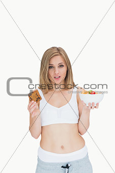 Portrait of young woman holding cookie and fruit bowl