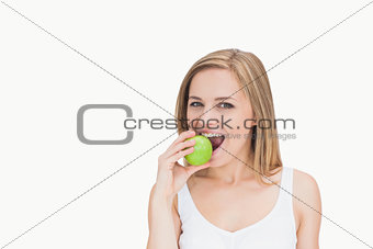 Portrait of young woman eating green apple
