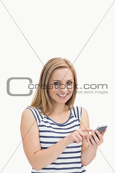 Portrait of casual young woman with smartphone