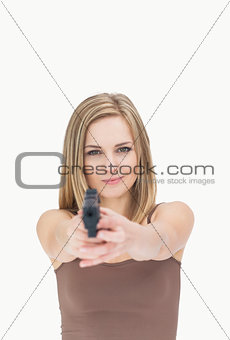 Portrait of casual woman aiming gun towards you