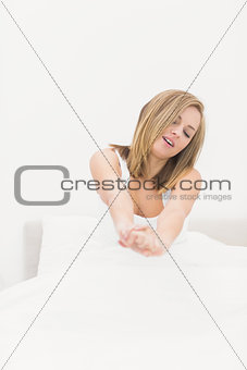 Sleepy woman stretching in bed