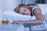 Asleep woman and spilt bottle of pills in bedroom