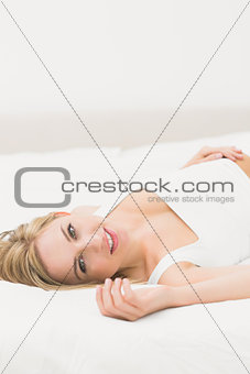 Portrait of young woman lying in bed