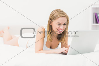 Beautiful happy woman lying in bed and using laptop