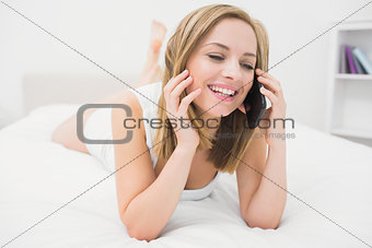 Casual young woman using mobile phone in bed