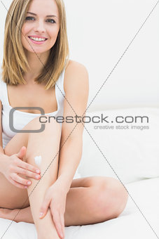 Portrait of woman applying cream on leg while sitting on bed