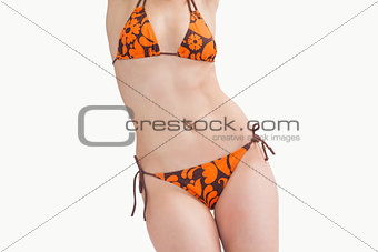 Midsection of young woman posing in bikini