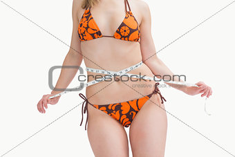 Midsection of young woman in bikini measuring waist