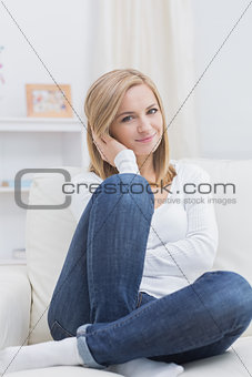 Portrait of relaxed woman sitting on sofa