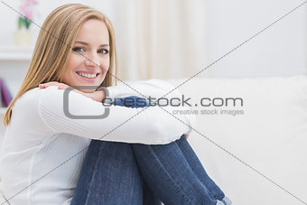 Portrait of casual happy woman sitting on sofa