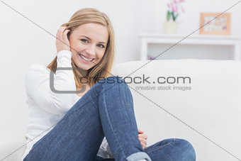 Portrait of casual young woman sitting on sofa
