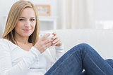 Woman with coffee cup sitting on couch