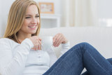 Woman with coffee cup day dreaming on couch