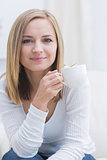 Portrait of woman with coffee cup sitting on couch