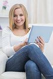 Portrait of casual happy woman using digital tablet on sofa