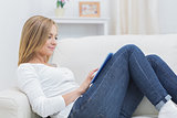 Side view of casual woman using digital tablet on sofa
