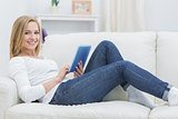 Portrait of happy casual woman using digital tablet on sofa