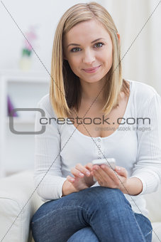 Portrait of young woman with mobile phone at home
