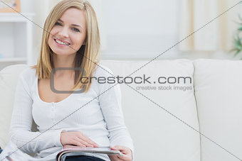 Portrait of happy woman with magazine at home