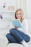 Happy young woman reading storybook at home